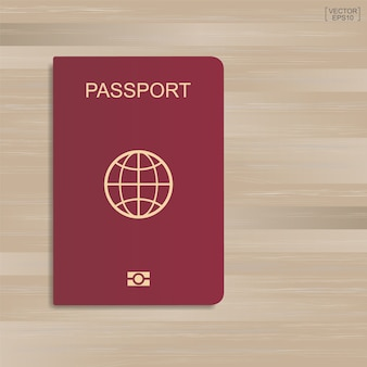 Passaporte vermelho no teste padrão e no fundo de madeira da textura.