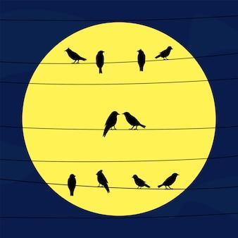Pássaros nos fios na luz da lua cheia