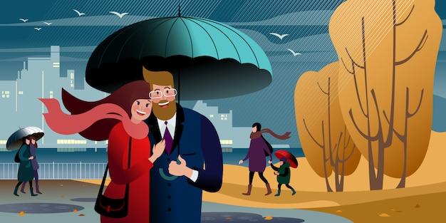 Passeio de um jovem casal no parque da cidade outono sob um guarda-chuva. cena de rua da cidade.