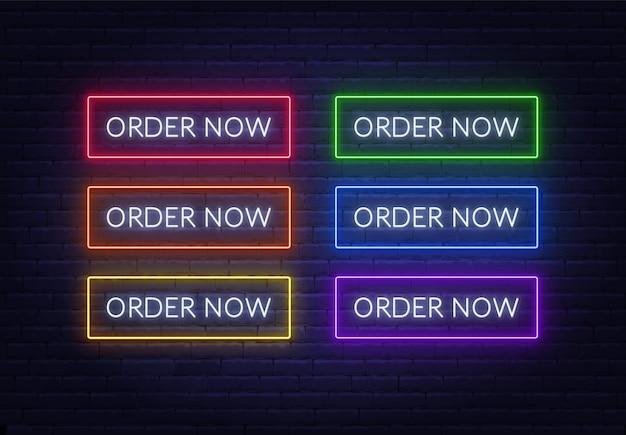 Peça agora o sinal de néon em um fundo de tijolo. botões brilhantes multicoloridos.