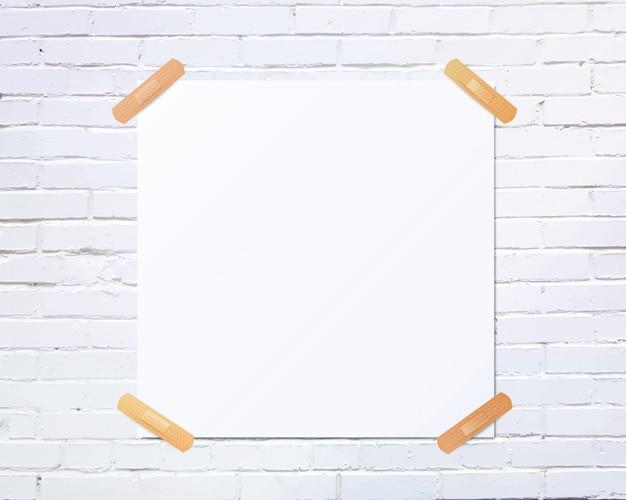 Pedaço de papel quadrado branco em branco colado na parede de tijolo branco