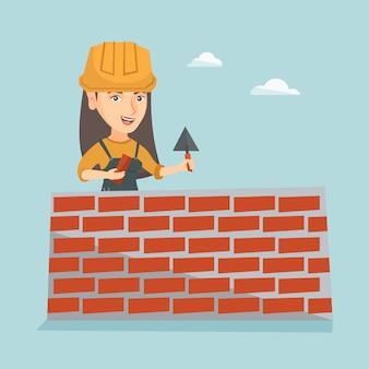 Pedreiro caucasiano novo que constrói uma parede de tijolo.