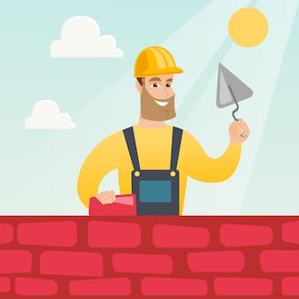 Pedreiro, trabalhando com espátula e tijolo.