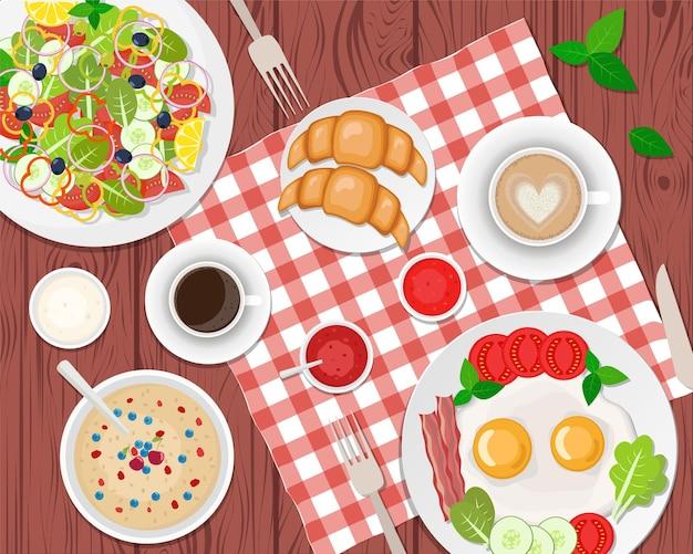 Pequeno-almoço saudável na mesa. ovos fritos, café, salada, torradas e croissants. apartamento
