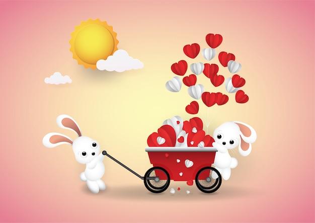 Pequeno coelho e mão carrinho coração de balão.