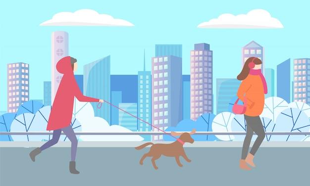 Pessoa com animal de estimação e mulher caminhando em winter park