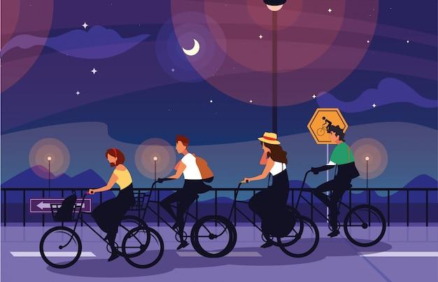 Pessoas andando de bicicleta na paisagem noturna com sinalização para ciclista