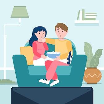 Pessoas assistindo a um filme em casa com pipoca