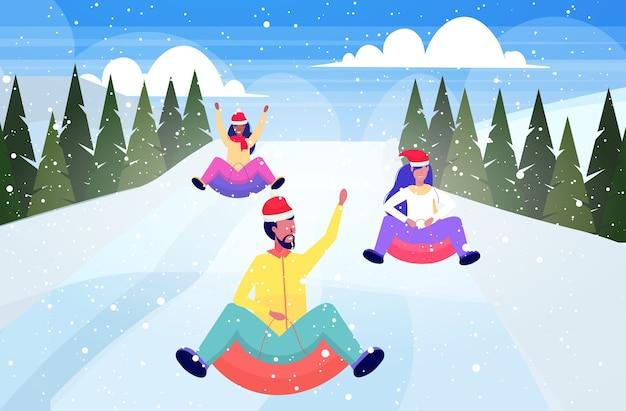 Pessoas com chapéus de papai noel andando de trenó na neve tubo de borracha natal ano novo inverno feriados atividades conceito amigos se divertindo paisagem de montanhas nevadas