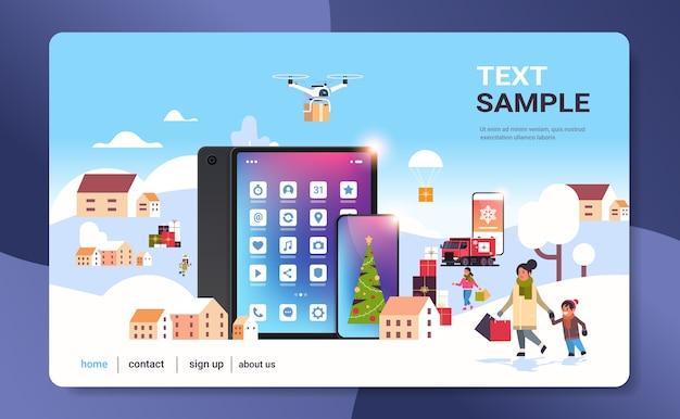 Pessoas com sacolas de compras caminhando ao ar livre usando o aplicativo móvel online se preparando para a página de destino do natal, ano novo, férias, paisagem urbana, inverno