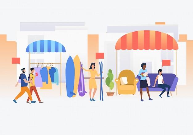 Pessoas comprando e vendendo roupas e esquis ao ar livre