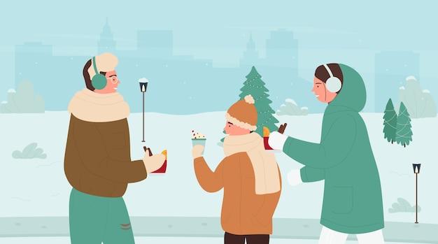 Pessoas da família bebendo bebidas quentes de inverno no parque de neve de inverno