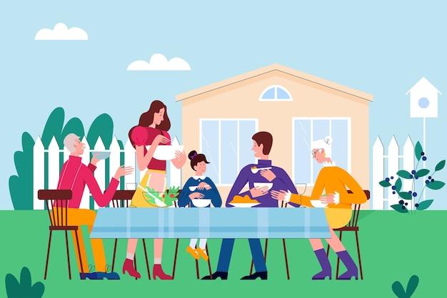 Pessoas da família comem em uma festa de piquenique no quintal