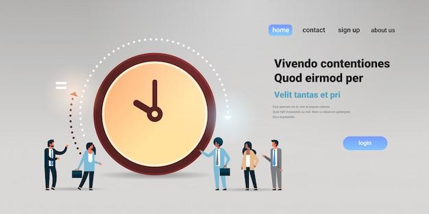 Pessoas de negócios se comunicando perto do prazo de gerenciamento de tempo do relógio grande