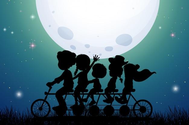 Pessoas de silhueta andando de bicicleta à noite