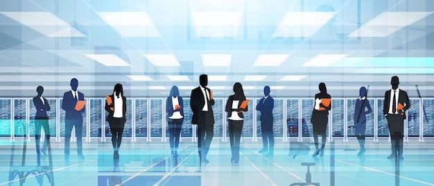 Pessoas de silhueta trabalhando no banco de dados de informações de computador de servidor de hospedagem de sala de centro de dados