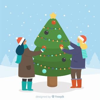Pessoas decorando a árvore de natal lá fora