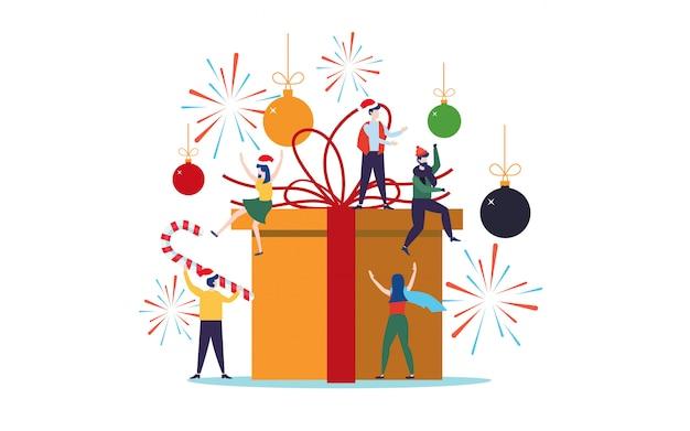 Pessoas decorando para o natal em uma grande caixa de presente