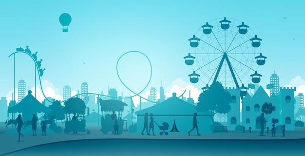 Pessoas e crianças se divertiam nos brinquedos do parque de diversões.