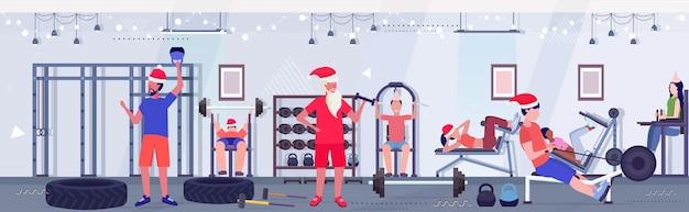 Pessoas e papai noel fazendo exercícios homens mulheres em chapéus treinamento treino conceito natal ano novo feriados celebração estilo de vida saudável moderno ginásio interior