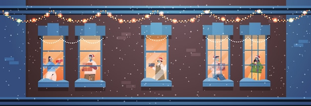 Pessoas em chapéus de papai noel segurando presentes misturam raça vizinhos em pé nas janelas ano novo natal feriados celebração auto-isolamento conceito construção fachada de casa ilustração vetorial horizontal
