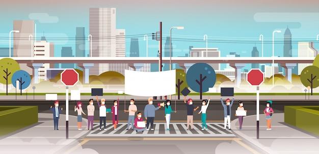 Pessoas em máscaras segurando cartaz e megafone na faixa de pedestres