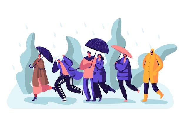Pessoas felizes e encharcadas de transeuntes, usando botas e mantos, com guarda-chuvas, caminhando contra o vento e a chuva