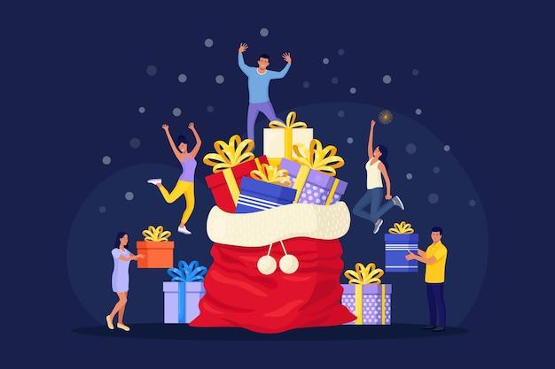 Pessoas minúsculas se preparam para a celebração do feriado de natal e ano novo. personagens carregam uma enorme caixa de presente perto do big santa sack com uma pilha de presentes e decoração festiva