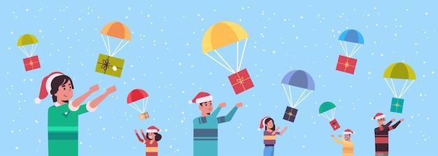 Pessoas pegando caixas de presentes caindo com pára-quedas feliz natal feliz ano novo feriado celebração conceito homens mulheres vestindo chapéus de papai noel ilustração vetorial retrato horizontal