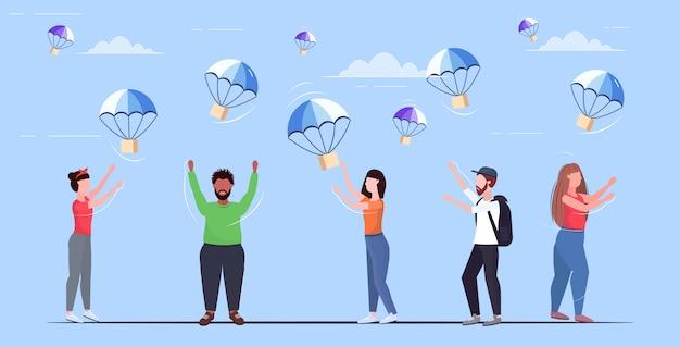 Pessoas, pegando, caixas pacote, caindo, com, pára-quedas, de, céu, transporte, pacote, correio aéreo, expresso, entrega postal, conceito, comprimento total, horizontal