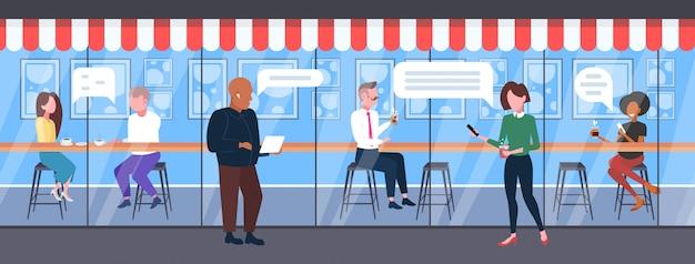 Pessoas que usam aparelhos digitais bate-papo móvel app bate-papo bolha social media comunicação conceito homens mulheres se divertindo moderno café exterior comprimento total horizontal