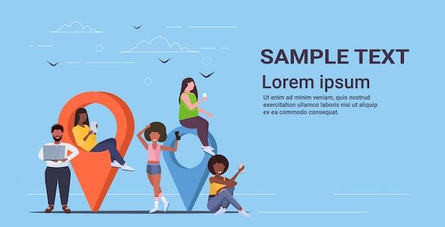 Pessoas que usam ponteiros geográficos coloridos misturam homens mulheres segurando dispositivos digitais perto de marcadores de localização gps conceito de navegação comprimento total de espaço horizontal