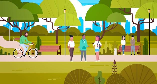 Pessoas relaxantes na natureza no belo parque urbano caminhadas equitação na bicicleta e se comunicando