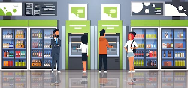 Pessoas retirando dinheiro terminal de pagamento em caixas eletrônicos perto de freezer de bebidas