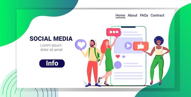 Pessoas segurando ícones de mídia social rede bate-papo bolha conceito de comunicação misture corrida homens mulheres usando o aplicativo móvel on-line esboçar espaço de cópia horizontal de corpo inteiro