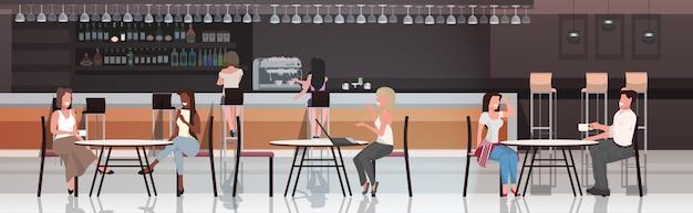 Pessoas sentadas nas mesas de café, bebendo café discutindo durante reunião
