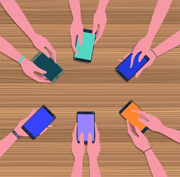Pessoas usando smartphones na mesa