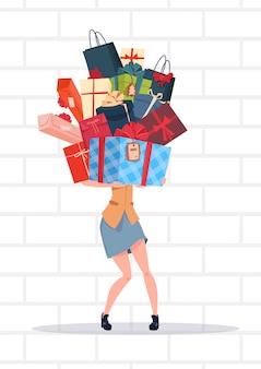 Pilha de caixas de presente de exploração de mulher sobre férias de fundo de parede de tijolo branco apresenta o conceito