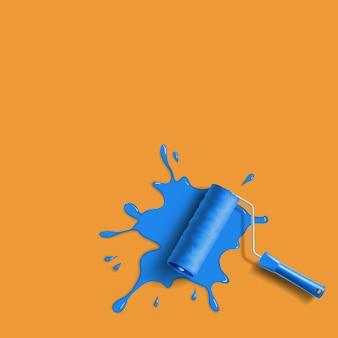 Pincel de rolo com respingos de tinta azul na parede laranja