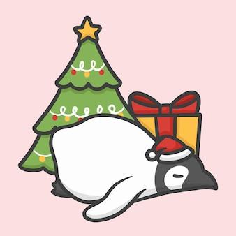 Pinguim dormindo com caixa de presente e árvore de natal
