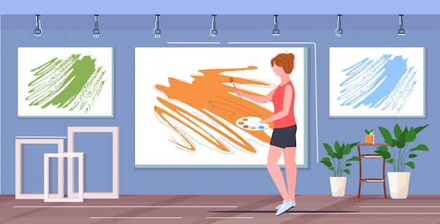 Pintor feminino usando pincel e paleta mulher artista de pé e retrato de pintura na parede arte conceito moderno estúdio interior galeria