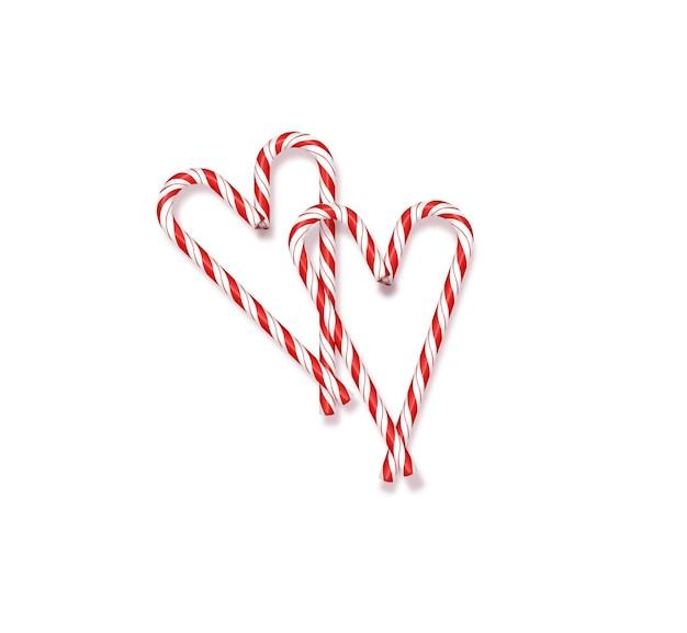 Pirulitos de natal vermelho e branco em um fundo branco forrado em forma de coração de natal e v ...