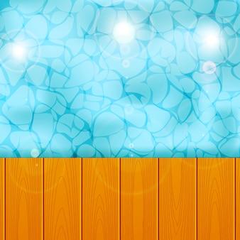 Piscina com praia no fundo da plataforma de prancha de madeira