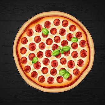 Pizza de calabresa redonda com queijo e manjericão em fundo preto