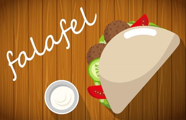 Placa de falafel com pão pita na mesa de madeira.