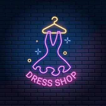 Placa de luz neon da loja de roupas na parede de tijolo escuro