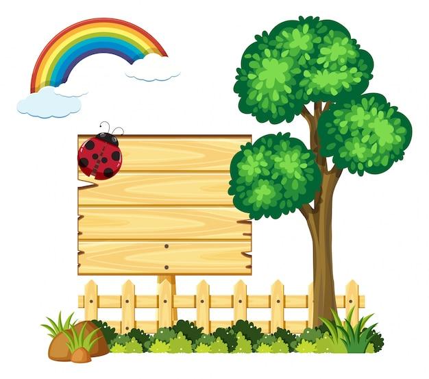 Placa de madeira no jardim com árvore e arco-íris