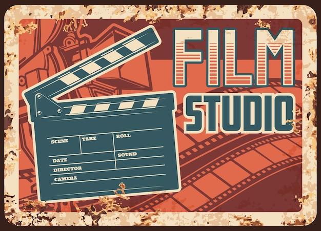 Placa de metal enferrujada de estúdio de cinema com câmera de claquete e tira de filme