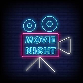 Placa de néon de noite de cinema na parede de tijolo