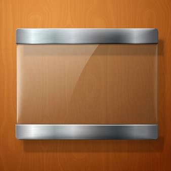 Placa de vidro com suportes de metal, para sua sinalização, sobre fundo de madeira.
